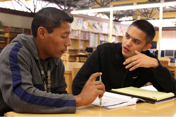 Senior Salvador Pasillas volunteers his afternoon to help one of the tutees with questions in a booklet compiled of practice California High School Exit Exampination questions.