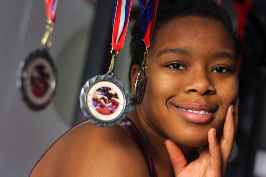 Brittany Marshal shows off her medals. The junior is a three-time district and regional wrestling champion and begins competing in the state tournament today. Allison Grimaldo photo.