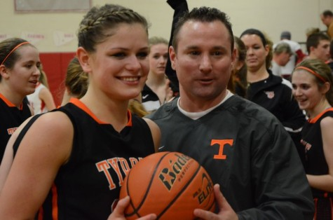 Jordan Swogger and Coach Luke Rhoades pose with the ball from the game where Swogger achieved the milestone of 1,000 career points.