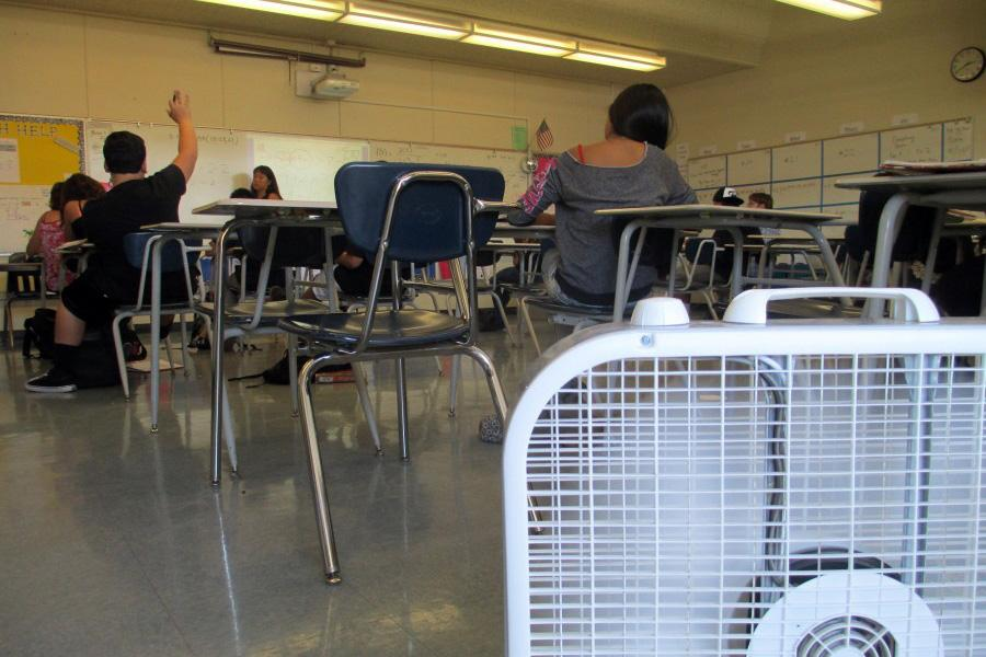Mrs. Katie Frederick teaches as her two fans guard the classroom's entrance in an attempt to combat rising temperatures at Camarillo High School in California.