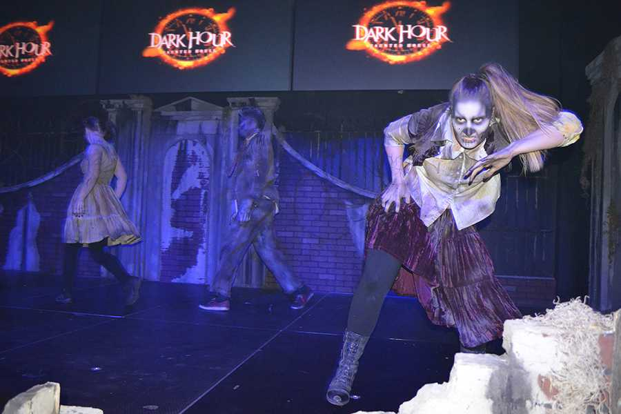 Zombies break dance on stage to entertain guests awaiting their haunt.