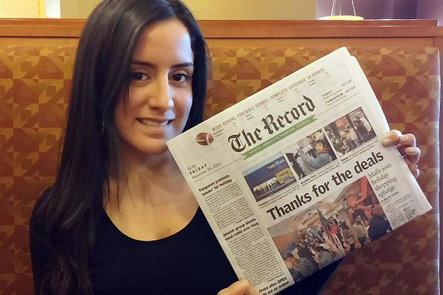 Melanie Anzidei, Class of 2009, holds up her front page story, which recently ran in The Record.