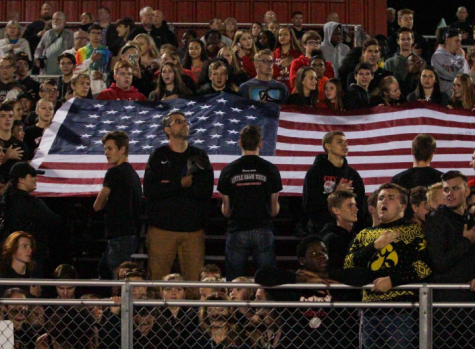 Students Kneel and Display Flag During National Anthem