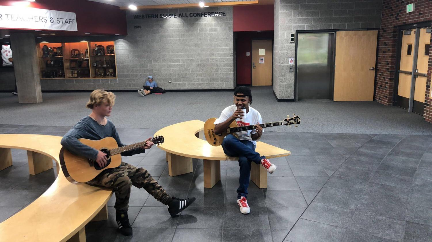 Two band students practicing the guitar.