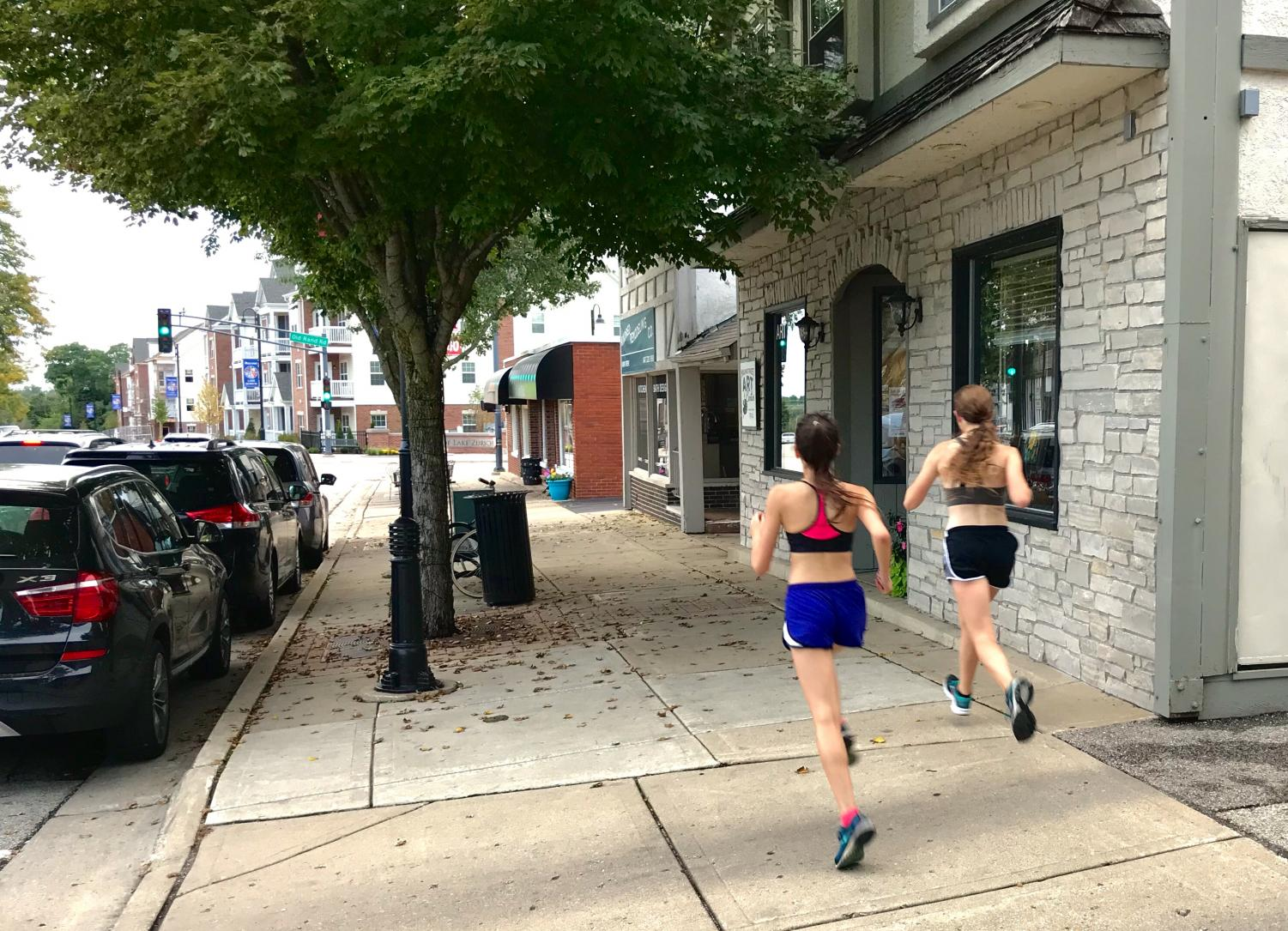 Two members of the girls cross country team run through downtown LZ. Even on runs like these, female runners say that they have to stay cautious of any threats that may come their way.