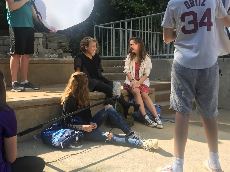 Actors Haley Henderson, Anne Rogan, and Abbie Feldman take a break as the production team prepares for the next take.
