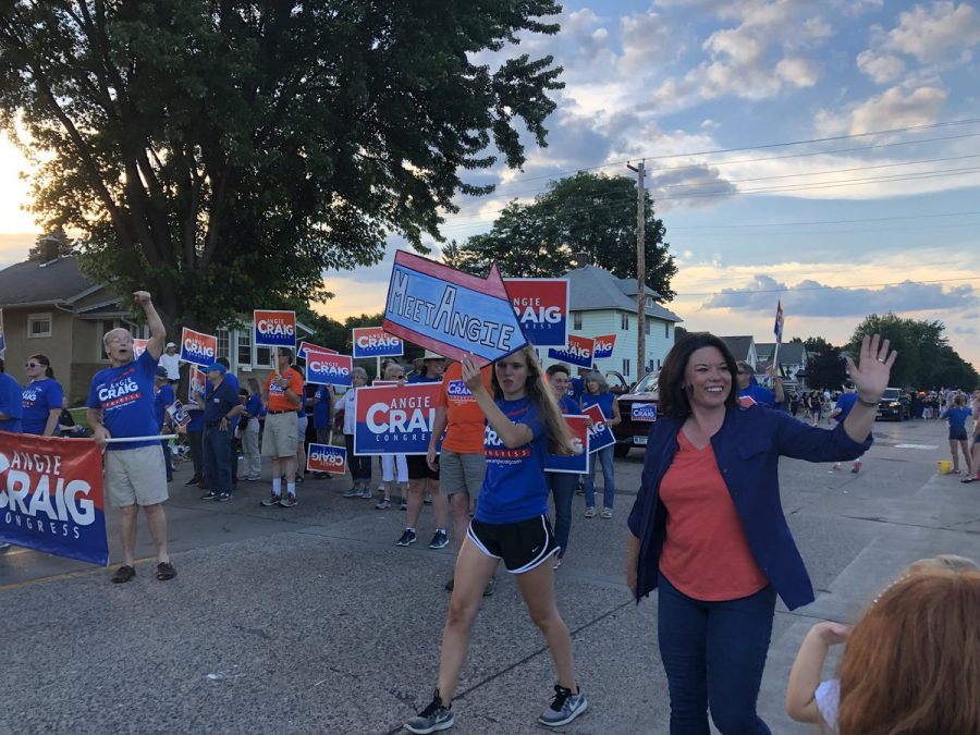 Kaia+Larsen+holds+a+sign+pointing+toward+candidate+Angie+Craig+at+a+parade+this+summer.+%E2%80%9CTell+people+to+get+out+to+vote+on+November+6.+Register+to+vote%2C+that%27s+really+important%2C+%5Band+don%E2%80%99t+forget+to+vote+and%5D+use+your+voice%2C%E2%80%9D+Larsen+said.