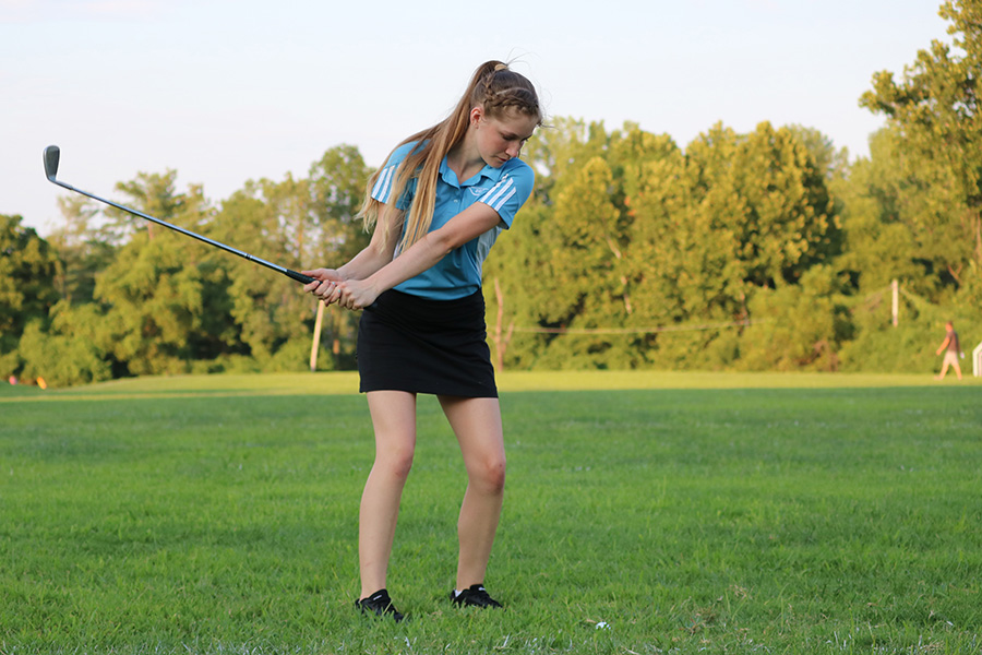 """Chipping her ball at a target, junior Ava Pfeil shows off her skills at Red and Blue night. This is her first year on the team, one of six new people on JV. """"I decided to join [golf] because I wanted to do another sport in the fall [in addition to cheer] and golf seemed like the most fun one because you can chill with friends and relax,"""" Pfeil said. """"My favorite part of the season has been the team bonding because since we're a small team we can get really close."""""""