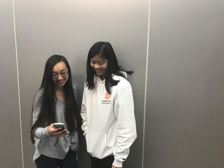 Woodside juniors Taila Lee and Emma Chiu look at the @wwoodsidememes page