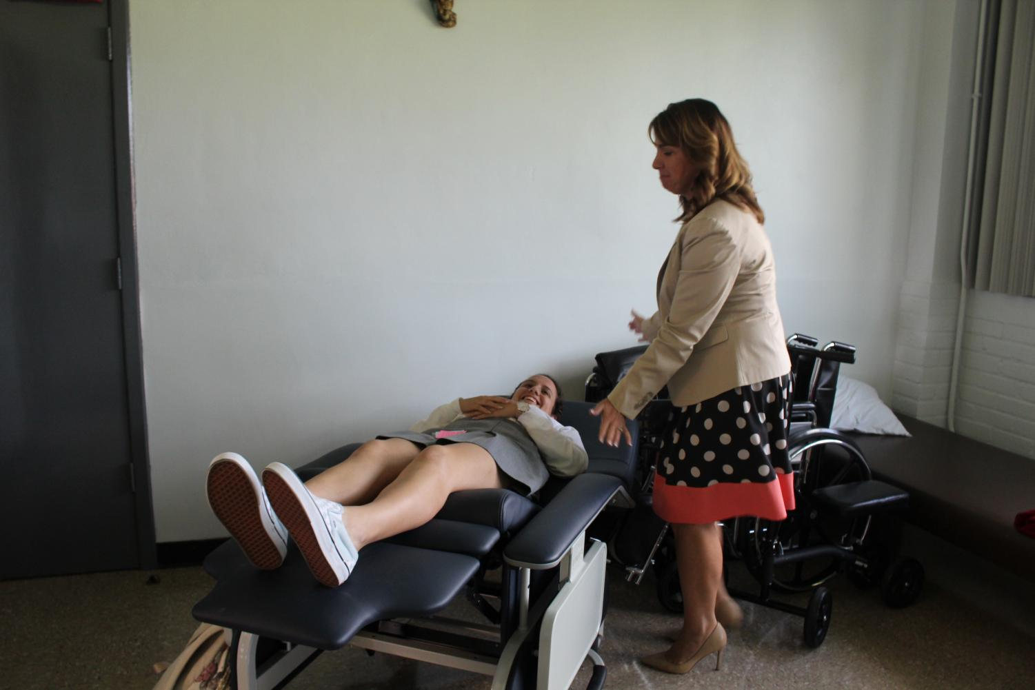 HELPING HAND: Nurse Shannon Brown 92' puts Victoria Geolonka on the trendelenburg position chair. Geolonka came to the nurse's office because she had fainted and was starting to feel lightheaded again.