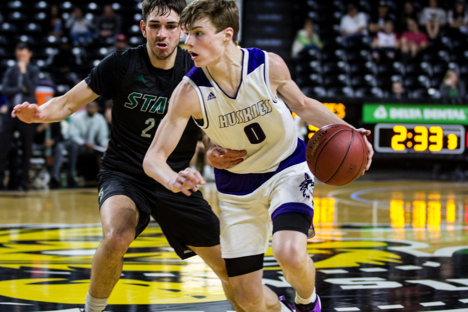Blue Valley Northwest junior guard Christian Braun (0) dribbles by Free State senior guard Zach McDermott during the third quarter of the Huskies matchup with Lawrence Free State March 10 at Charles Koch Arena. The Huskies defeated the Firebirds, 51-40.