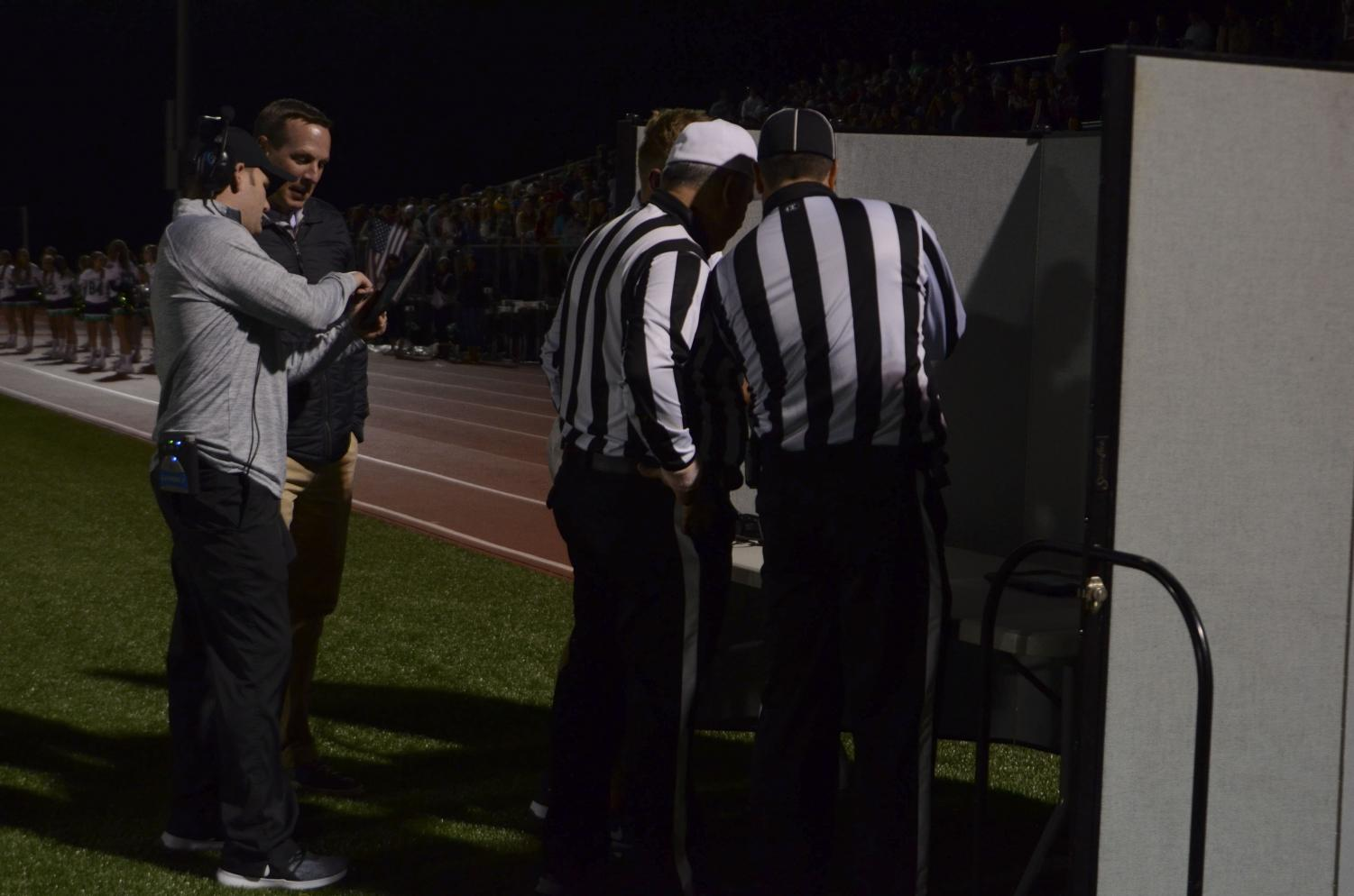 The referees review the play at the replay booth with PV assistant Coach JJ Moran, while defense coordinator Adam Preciado shows the play to Athletic Director Shawn Buchanan.