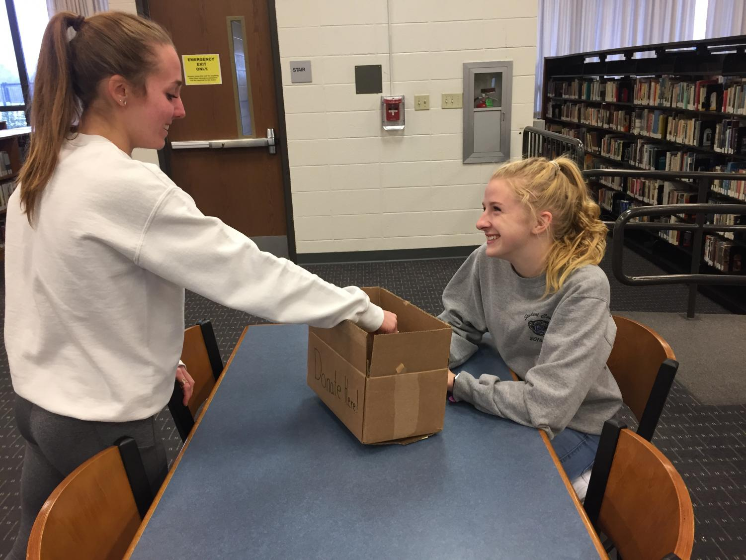 A student hands money to Jillian Baffa, senior (right), to donate to the Keep Swimming Foundation. The foundation is the chosen charity for Charity Bash this year, and clubs are already raising money in a variety of ways.