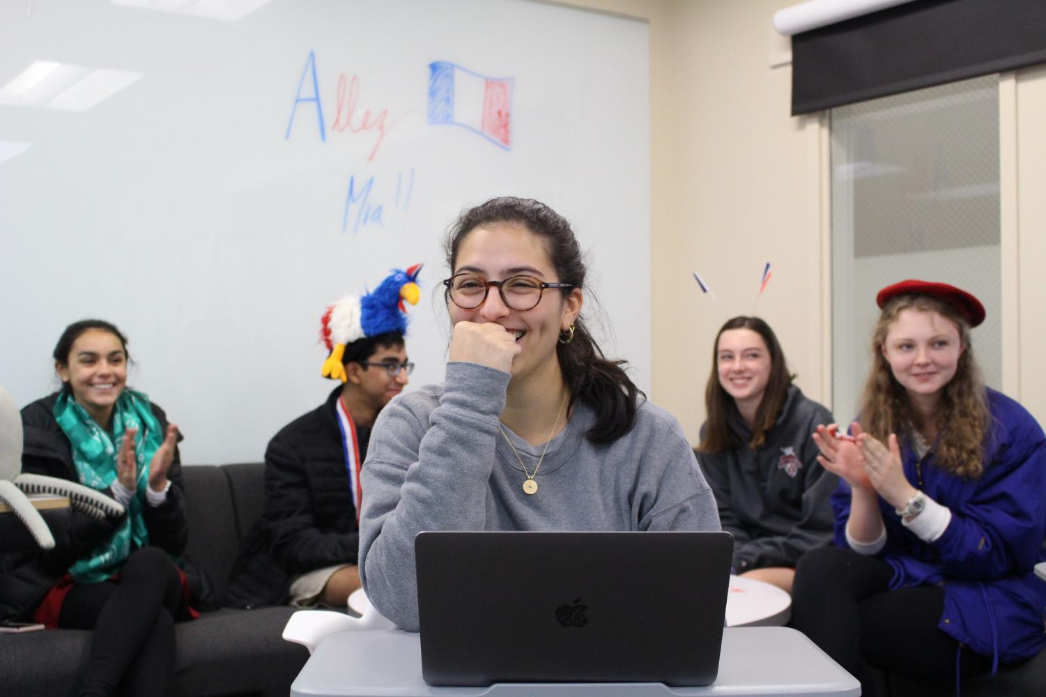 Junior Mia Fares competes in a nationwide French Kahoot! game while fellow peers encourage her.