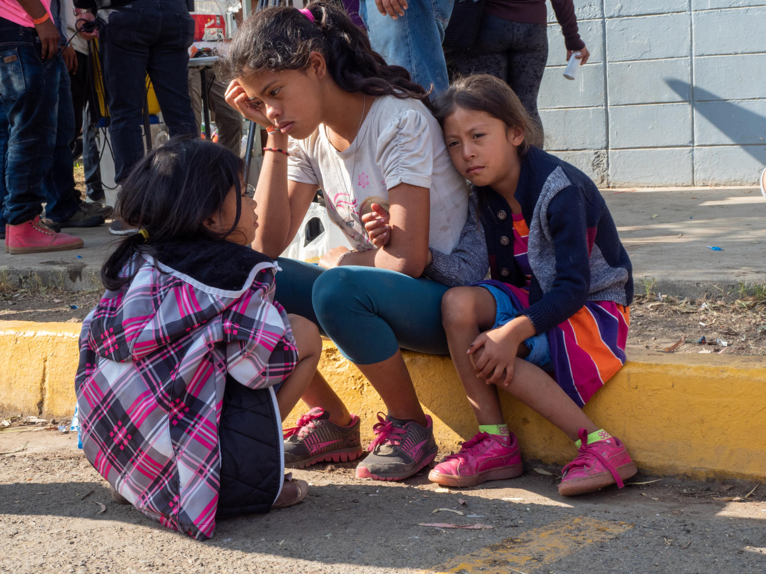 Three sisters sit on the curb in front of Benito Juarez sports center, worried about the disappearance of their mother, who left with a friend to find food the previous night.