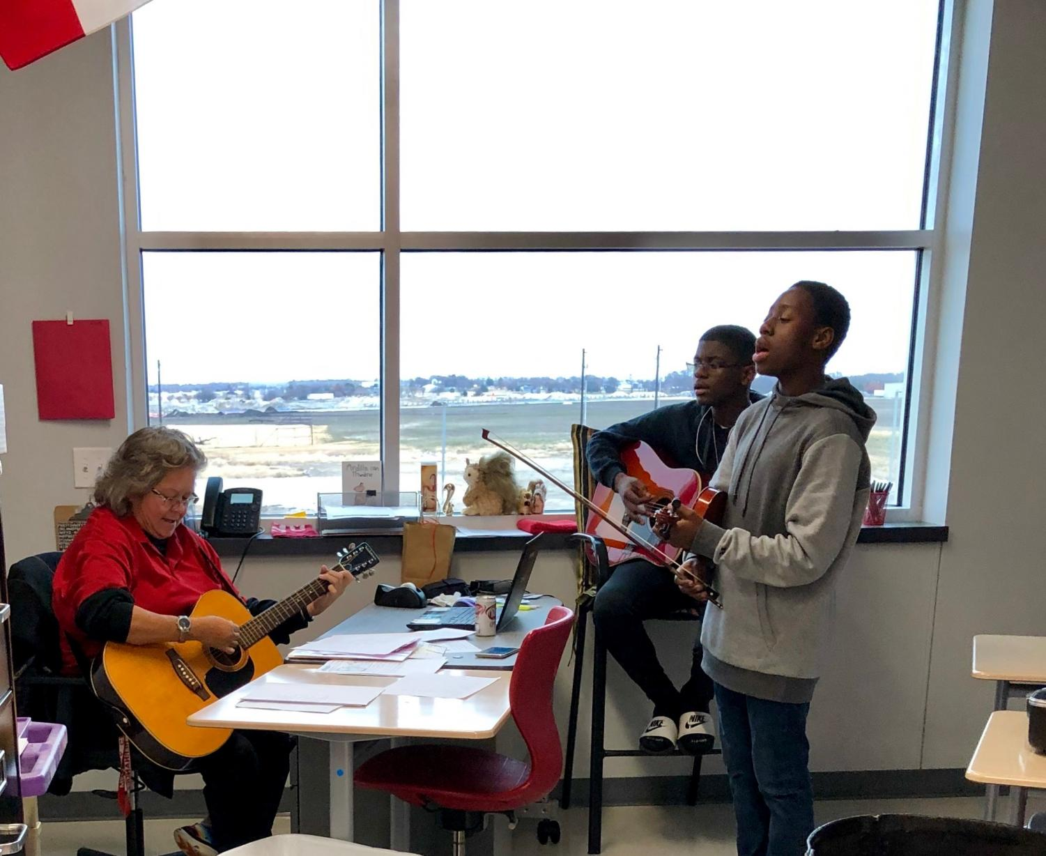 Mrs. Hernandez plays guitar with students during her Mega Lunch club Life Enrichment.
