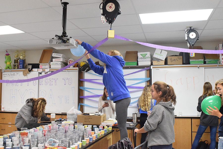 """Taping balloons to girls cross country coach Charles Cutelli's science room, the team fills his room with decorations to celebrate his birthday. The team used one of their many inside jokes with Cutelli to decorate his room. """"My favorite part of decorating was spending time with all the girls and just getting to have fun,"""" sophomore Claire Hardy said."""