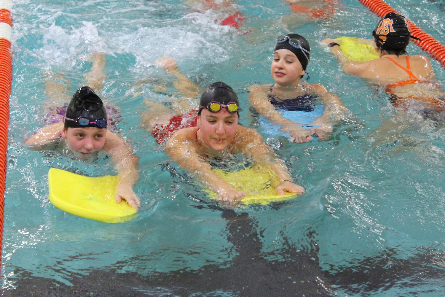 Eighth graders Quinn Hartnett, Caroline Forester and Stephanie Stone warm up in the swimming pool on kickboards during practice Oct. 22. Earlier this year the swimming pool wasn't its usual temperature.