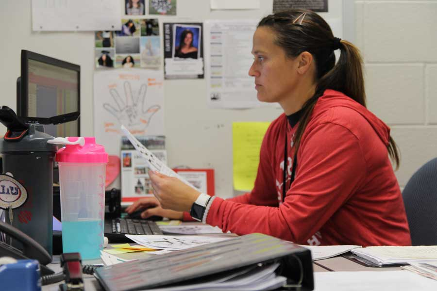 Coach Lacy Beckler works at her desk during her off period. Beckler works a second job to earn extra money.