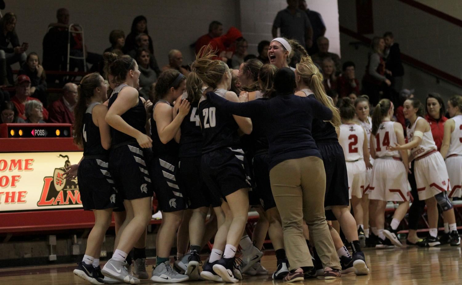 The Pleasant Valley Girls basketball team celebrates their victory against the 2nd ranked North Scott Lancers.