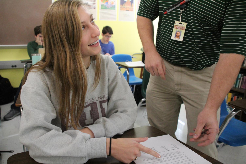 Mr. Dalton gives Jordyn Lodes help on her paper.