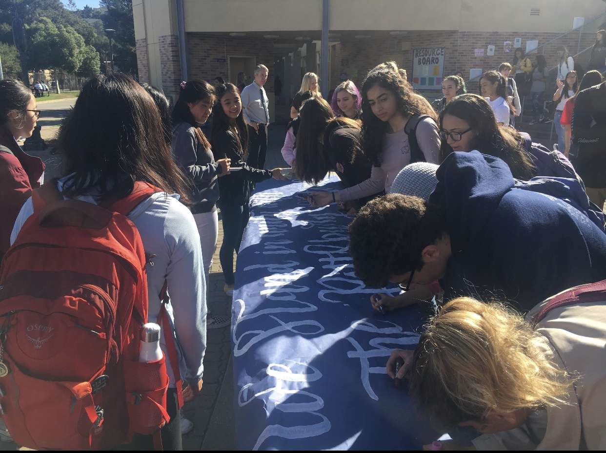 Students sign a poster to show their support against anti-Semitism.