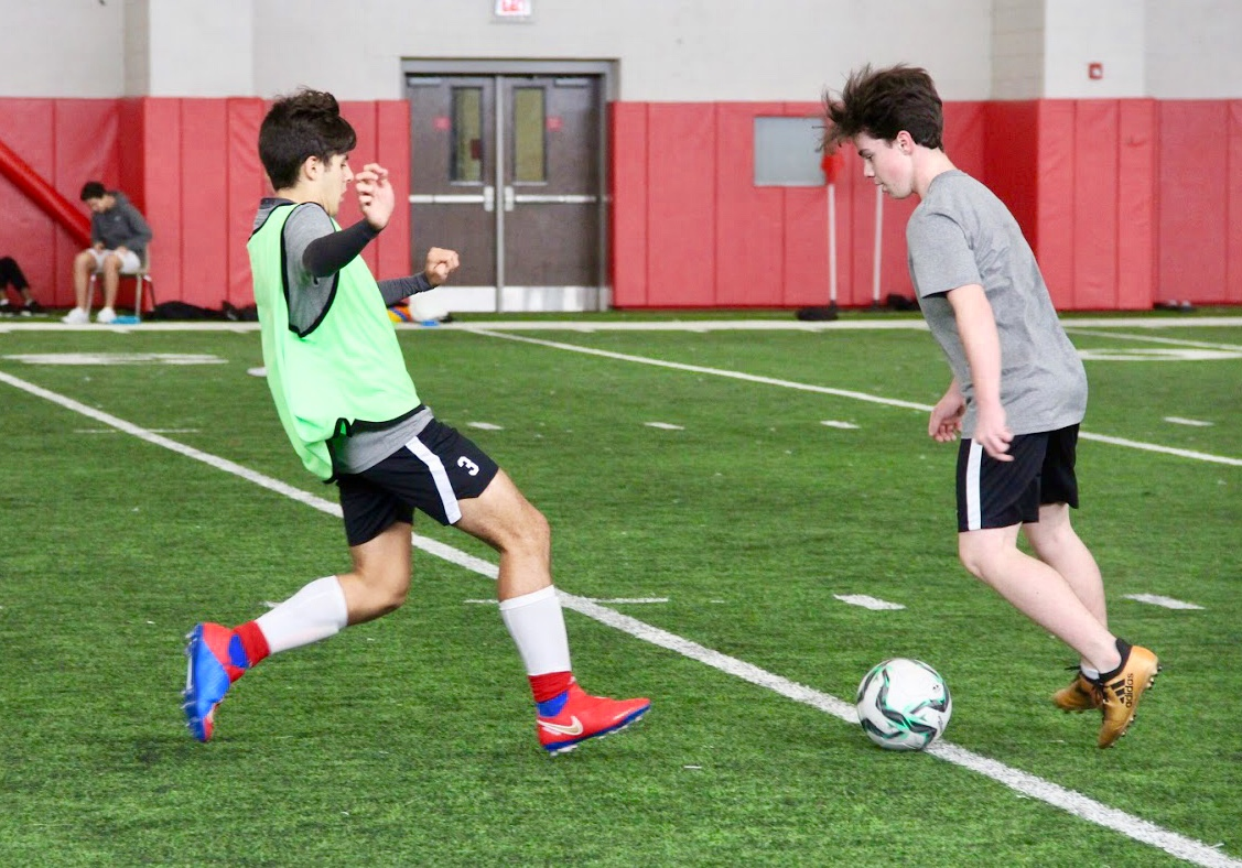 Coppell High School junior Richard Bracho defences the ball against Coppell High School sophomore Oliver Isenberg during practice in the fieldhouse on Nov. 28. Bracho is originally from Venezuela and moved to Kentucky two years ago, and this school year moved to Coppell where he enjoys his passion for soccer.