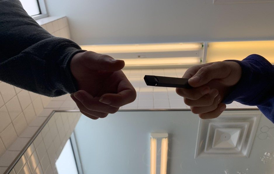 """Two freshmen pass what looks to be a USB flash drive to each other. Vaping in the bathrooms has become an prevalent issue at McCallum, raising concerns about the nicotine that students are inhaling. """"I need it to get through the day,"""