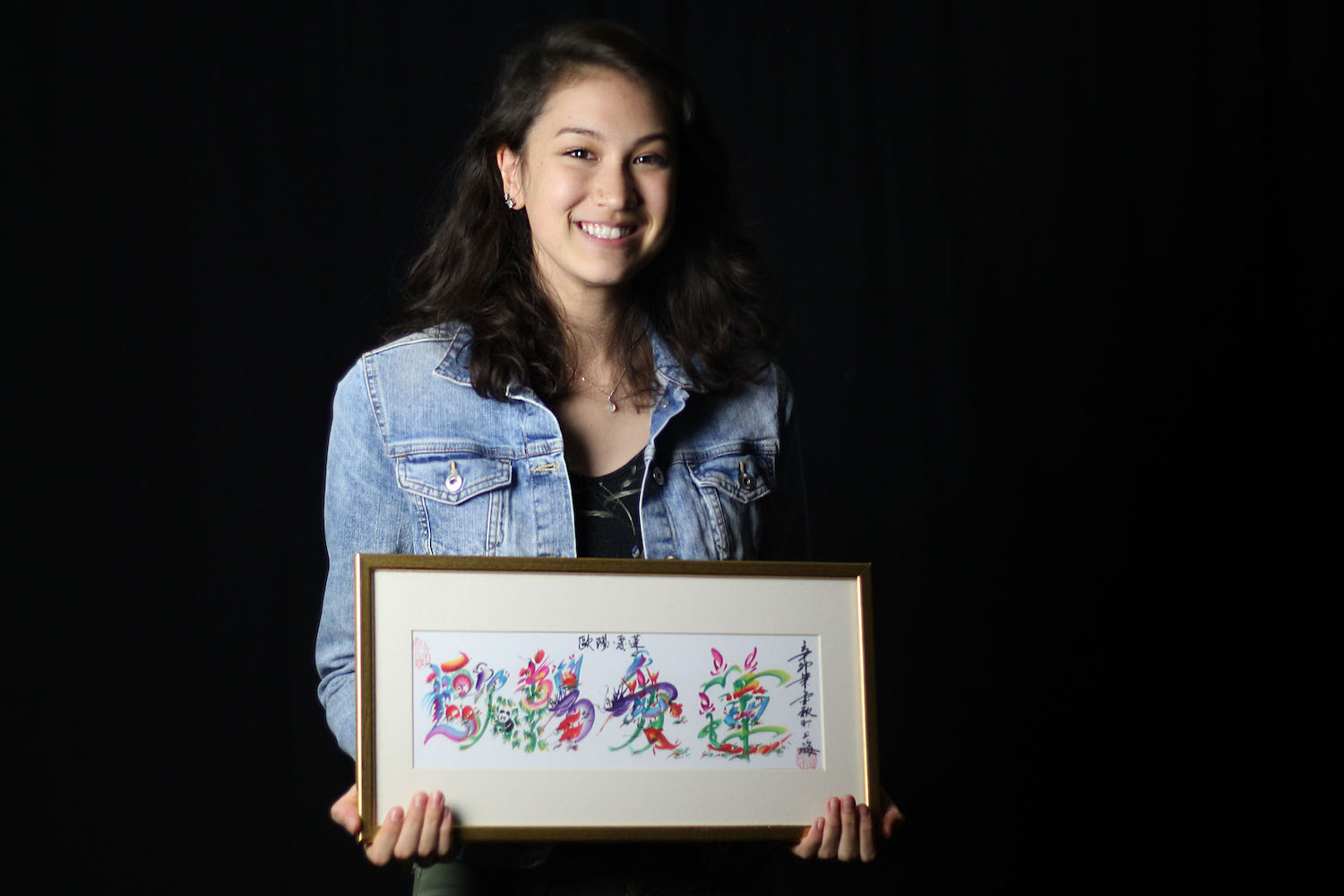 Arianne Ohman poses with a painting of her name in chinese.