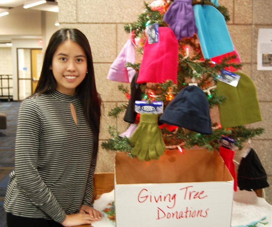 Senior+Truc+Nguyen+poses+by+the+Giving+Tree+on+Dec.+20+during+5th+hour+in+the+Library+Media+Center.