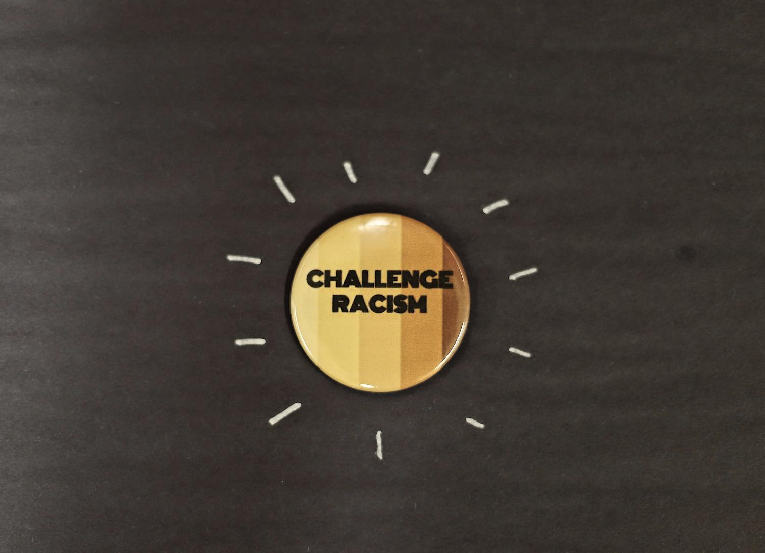 A student-created pin that encourages students to challenge racism.