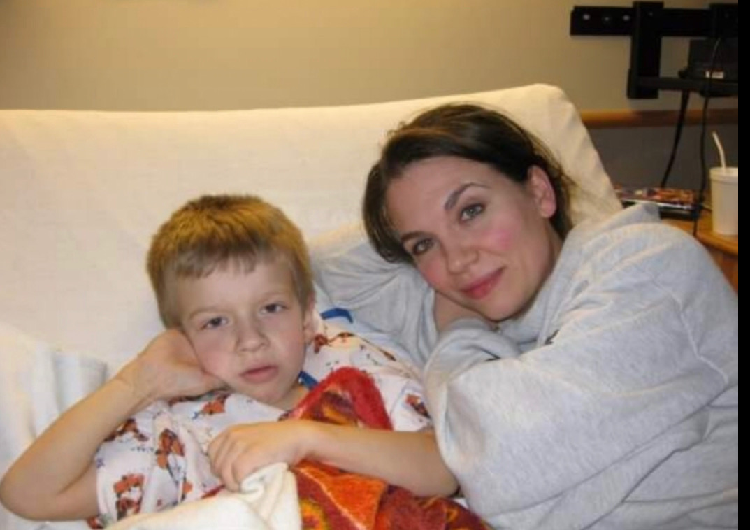 Mead lays in his hospital bed with his mom at the age of 9 after his transplant.