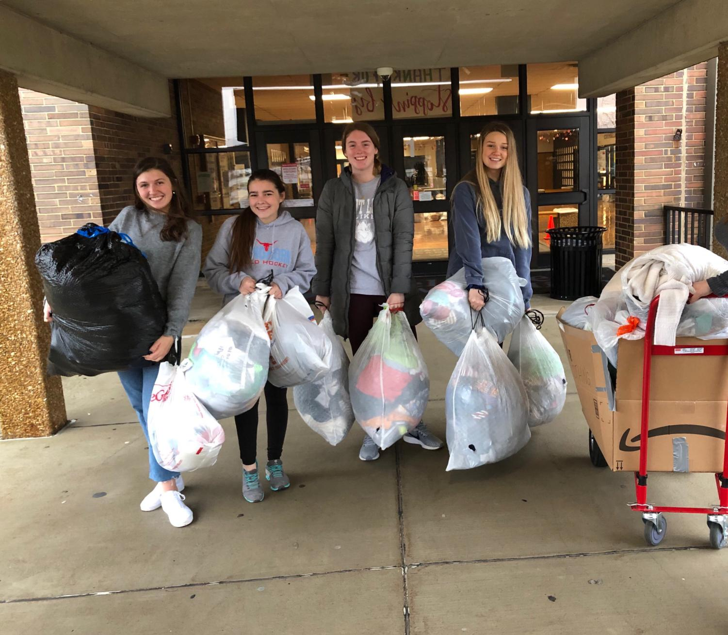 "Juniors Lily Stiegemeyer and Emma Caplinger and seniors Olivia Riemer and Hayden Sampson,  are carrying bags to the truck to load donations for St. Clair high school. Bags are being carried down and loaded onto a truck  to be taken to kids in need. ""In the morning at 7am, we carried  the bags down to the main floor, and they were all heavy. Klevens asked some of the guys that were sitting in the Art Foyer  to help us carry down the bags do it went a lot faster.""Yearbook Editor -in-Chief, senior Olivia Riemer said."
