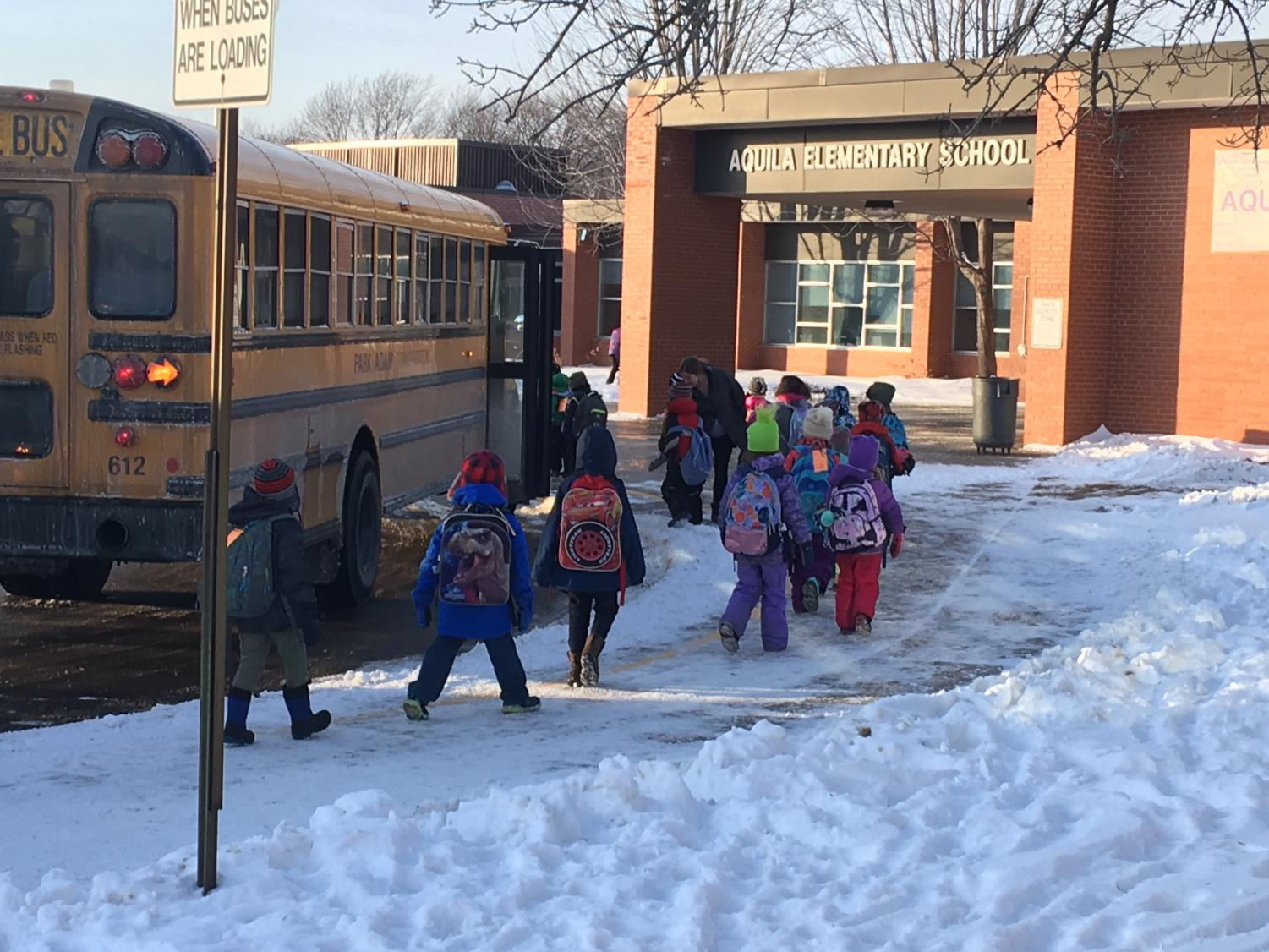 Students from Aquila board busses at the end of school Feb. 1.   Students were late in leaving school due to an extended evacuation because of a sprinkler head burst.