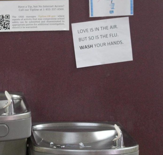 A+sign+above+the+water+fountains+in+the+eighth-grade+hall+remind+students+about+the+flu.