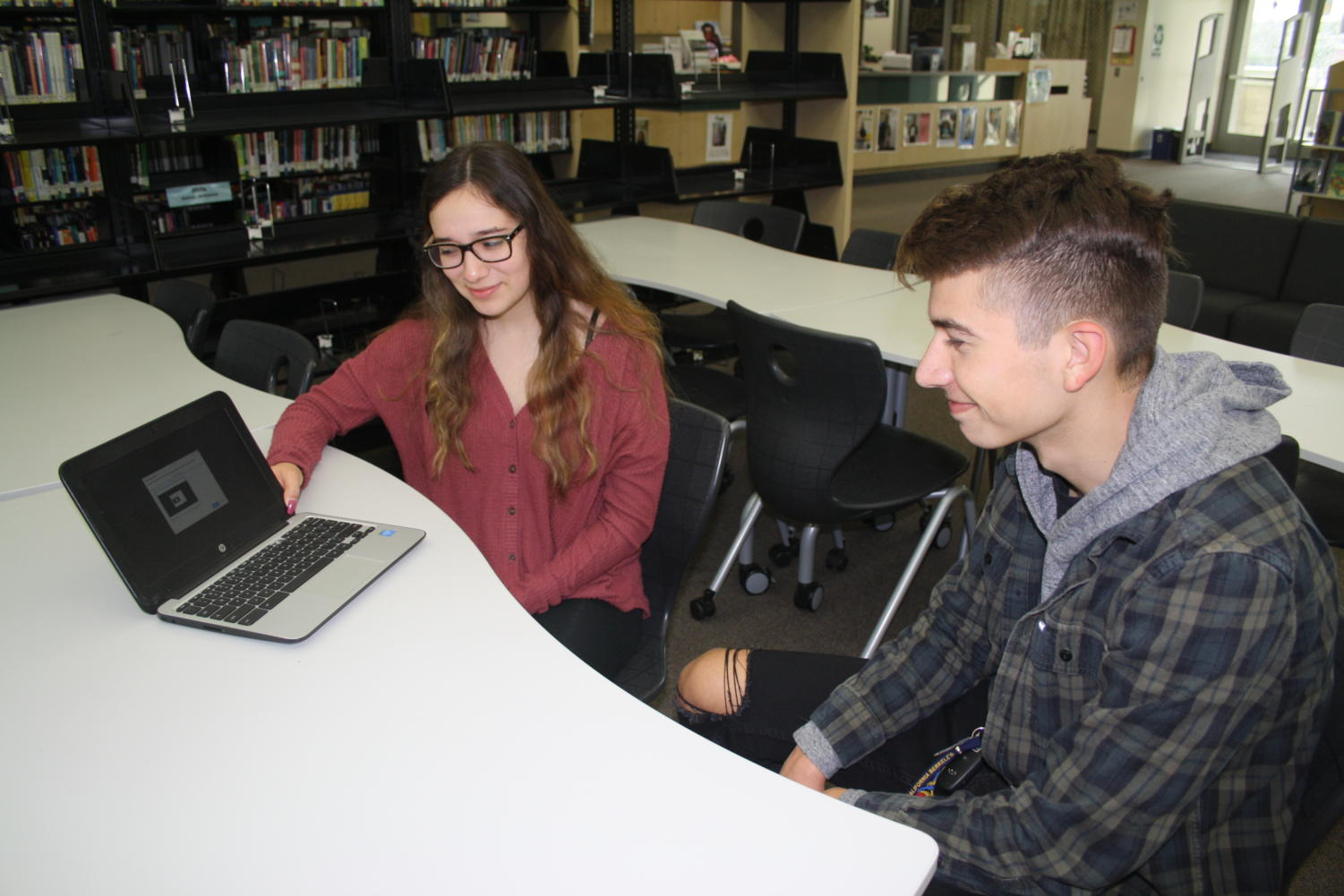 From Left: Godinez Fundamental High School seniors, Rachel Quezada and Nathan Escobedo are annoyed of the reoccurring LAN screen that appears each morning when they open their Chromebooks at school. Photo taken in the GFHS Library on January 30, 2019.
