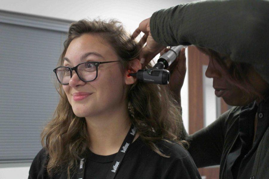 The+school+nurse+examines+sophomore+Della+Fowler%27s+ear+canal.+