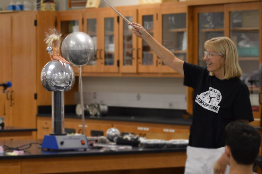 """Revolving a metal sphere around a Barbie doll, physics teacher Ellen Wilke explains the mechanics behind electricity. However, as much as Wilke enjoys explaining electricity, she would much rather explore optics. """"I really like [optics],"""" Wilke said. """"The way of optics is a really cool thing and allows you to work with material science, which is what my undergrad was, to work with the crystalline structure of substances. There's so many cool applications of optics. The basics will start with mirrors and lenses. Then, it's all about light and the reflection of light, and the different applications with lights and lasers."""""""