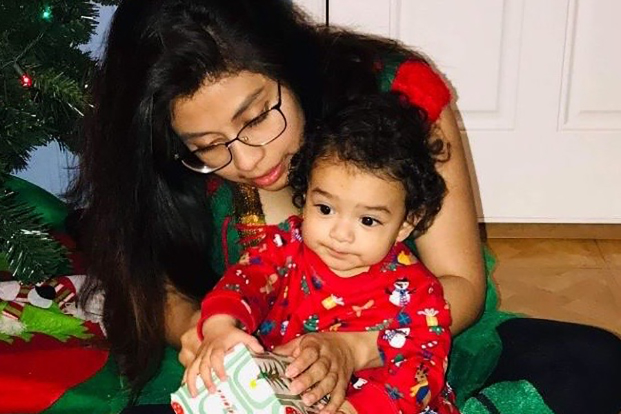 Senior Brenda Ayala unwraps gifts with her son, Liam.