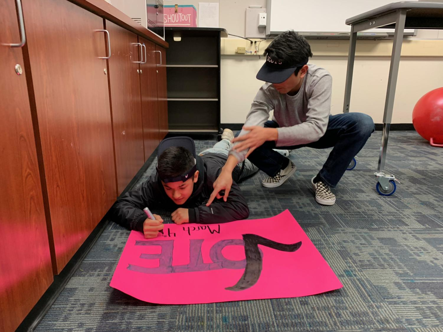 Freshmen Jono Sison and Nate Hsich create a poster publicizing the election.