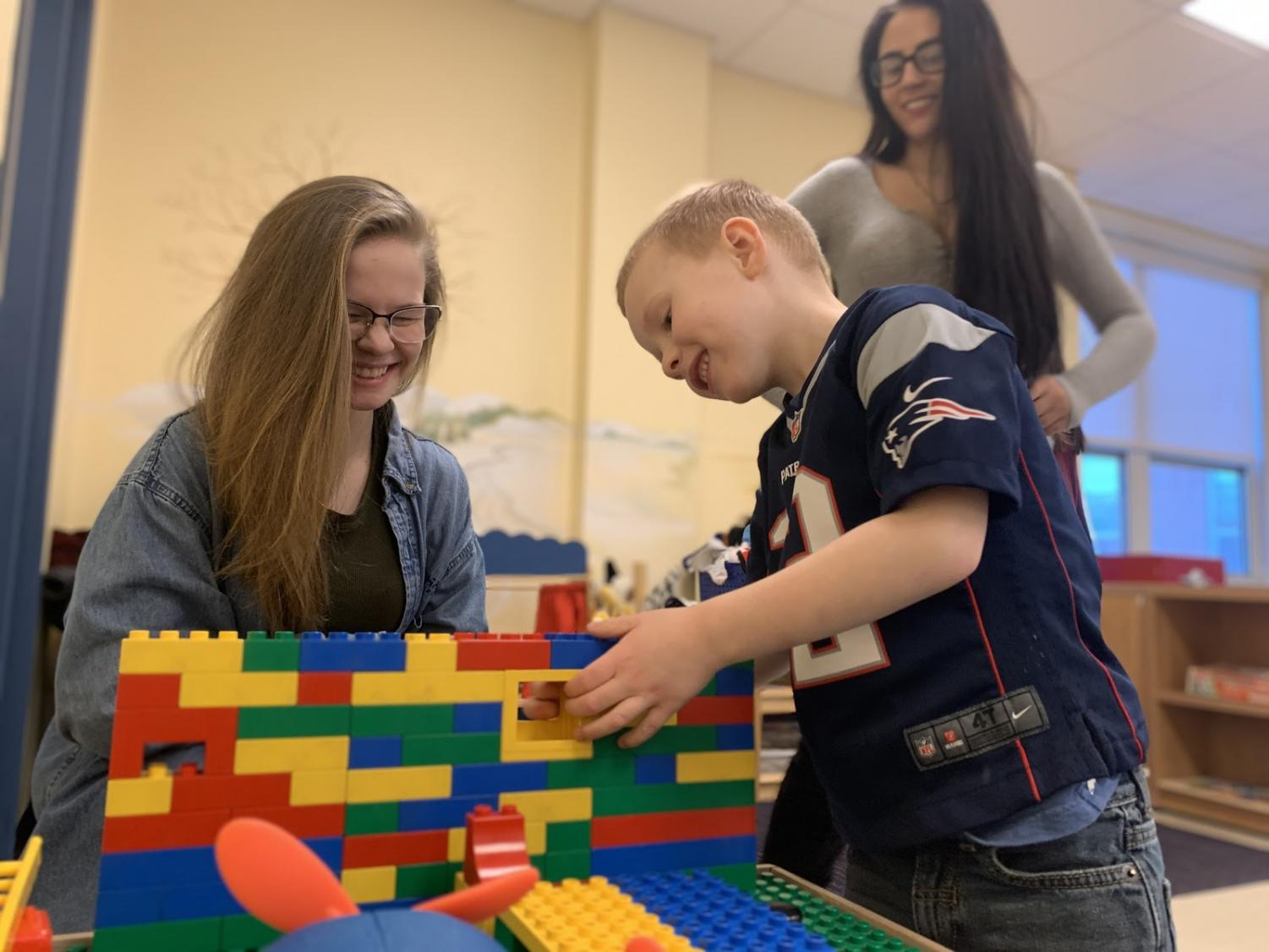 "Junior AbbyGaile Kieler [back right] and senior Elizabeth Rice are two of the high school students who takes the childhood development class. ""Its crazy; throughout my time here I watch them grow up and play with each other and really come out of their shells,"" Kieler said. Tiny Tomahawk James makes some finishing touches on his lego house with the help of his student teachers."