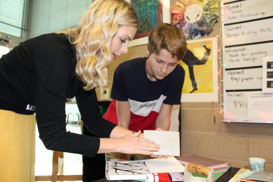 Megan+Herrick+helps+a+student+create+a+piece+of+art+during+class.+She+gave+him+new+ideas+and+helpful+guidance+for+finishing+his+artwork.+