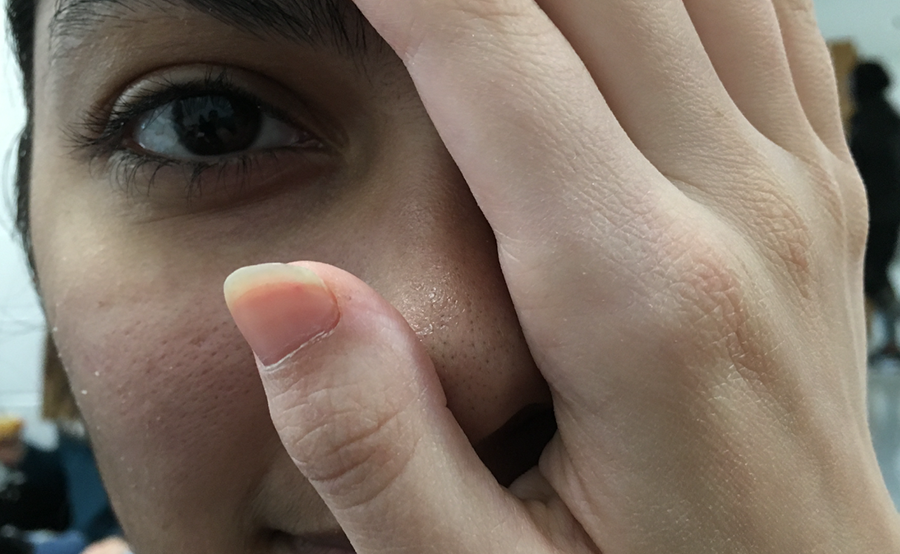 Junior Dhara Padhiar covers her face with white hands, depicting the double standard society has put on her. Society tends to cause problems for kids who identify with two cultures because of the inability to see them in more than one way.