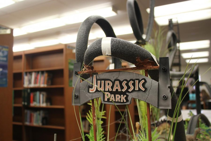 The+Jurassic+Park+sign+hangs+from+the+track+of+an+academic+physics+roller+coaster+in+the+library.+The+coaster+had+many+loops%2C+curves%2C+and+inclines+included%2C+as+students+were+graded+on+the+features+of+their+coaster.