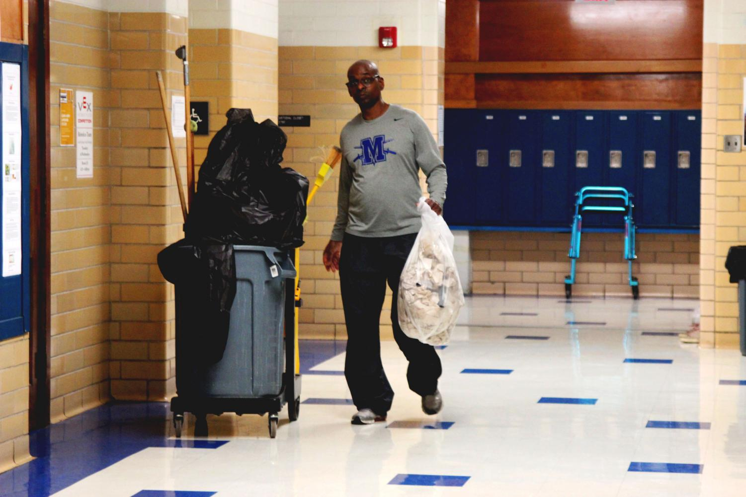 "A HARD DAY'S KNIGHT: Working hard to keep McCallum clean, janitor Kenneth takes out the trash from the boys bathroom. After finishing the boys bathroom, he cleaned the science hall. As ""I never decided to [be a custodian] initially,"