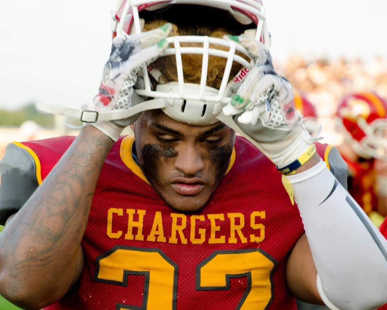 Senior Xavier Vaughn removing his helmet minutes before the Mangy Lion game at Charger Field on Aug. 17. 2018.