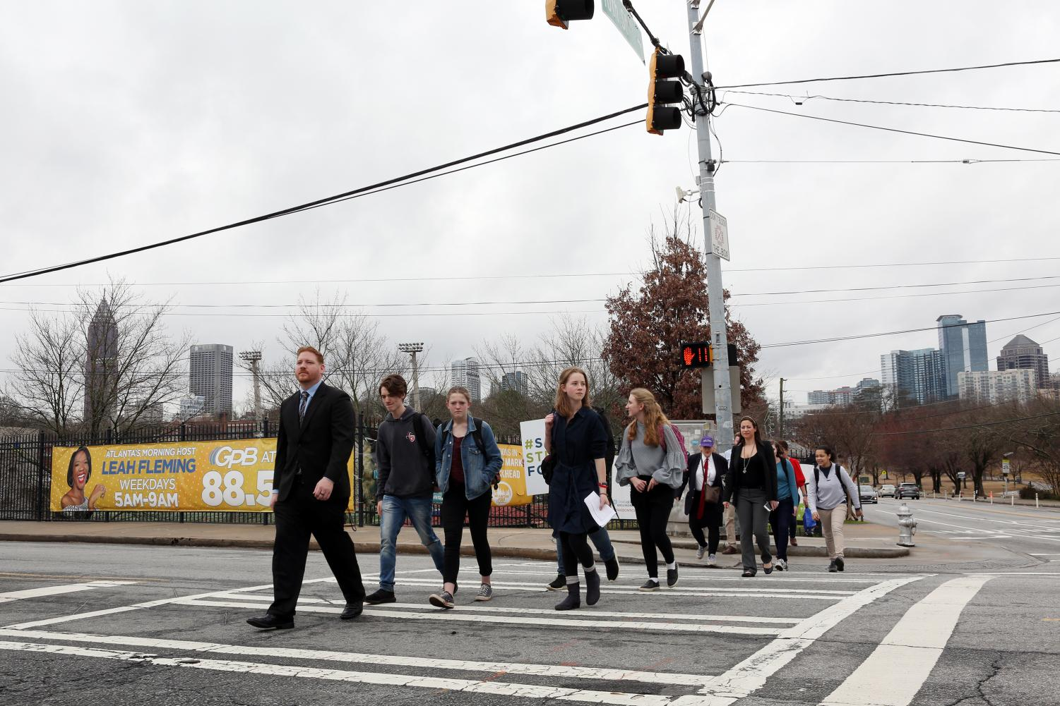 ORIGIN STORY: Thomas Hyneman and Grady Pedestrian Safety Coalition members cross 10th Street to visit a memorial for Hyneman's daughter, Alexia, who was killed at the intersection in February 2016.