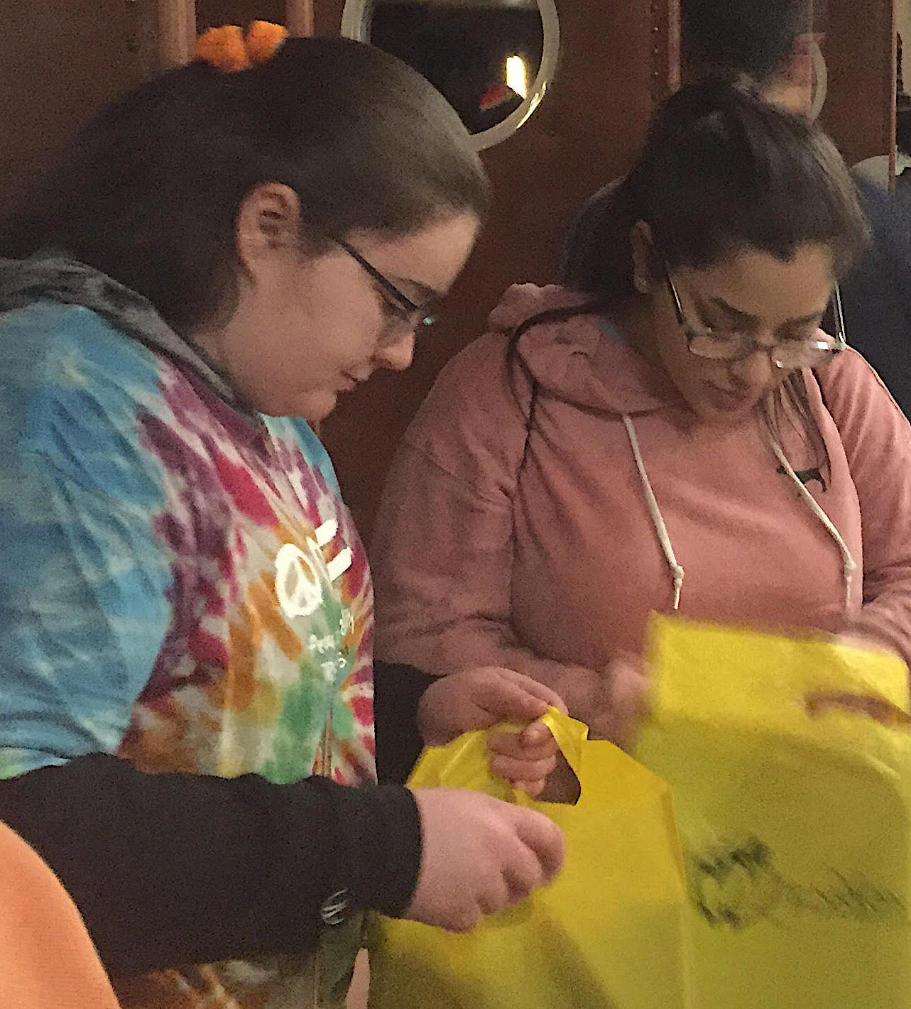 DHS students Ashley Schlemmer, left, and Angelina Campos look over the True Color Conference's materials and program.