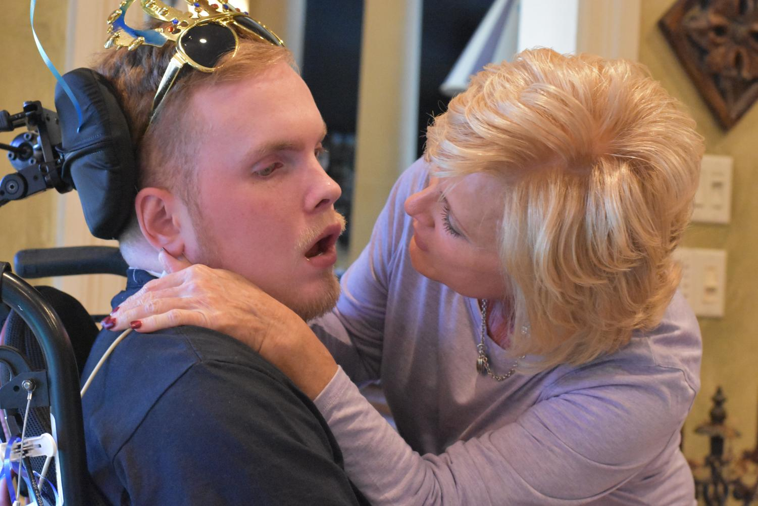 Terri Stanton leans in close to get her son Joseph's attention during his 25th birthday party. Stanton suffered a traumatic brain injury in a skateboard accident the summer after his sophomore year of high school. He was a state swimming champion at Kingwood Park and still holds three school swim records, despite only competing his freshman and sophomore seasons.