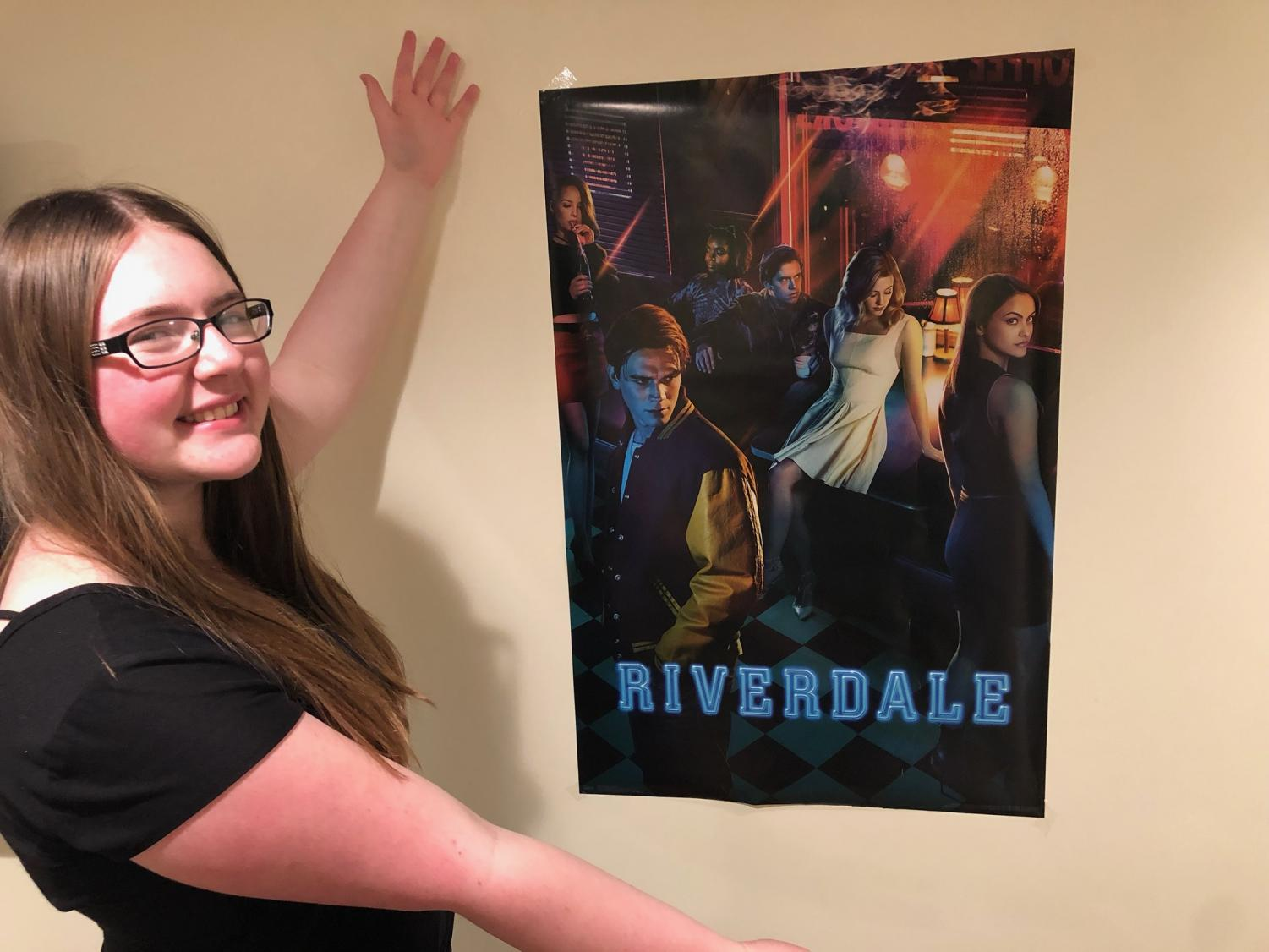Our Riverdale Reviewer poses before one of her favorite posters of one of her favorite shows.